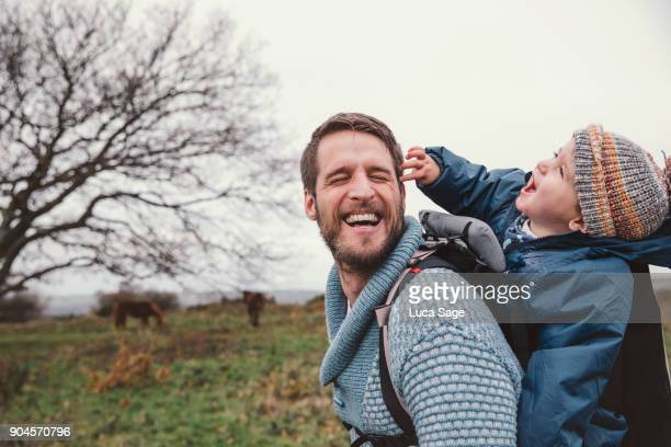 a father laughs share a funny moment whilst walking in the countryside - one parent stock pictures, royalty-free photos & images