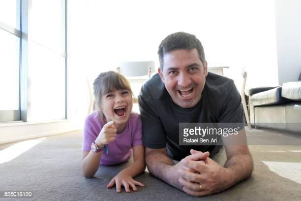 father laughs with his daughter at home - rafael ben ari fotografías e imágenes de stock