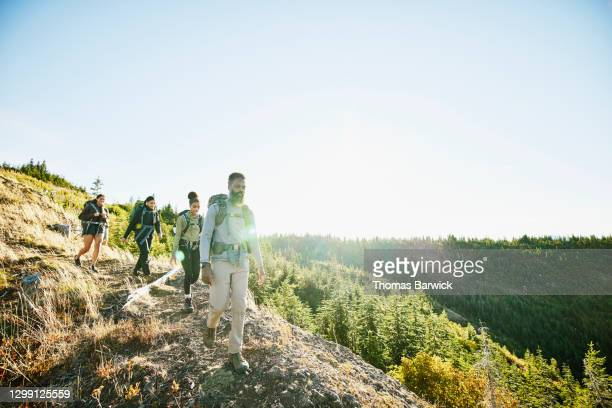 father leading daughters along ridge during backpacking trip on fall afternoon - nature stock pictures, royalty-free photos & images