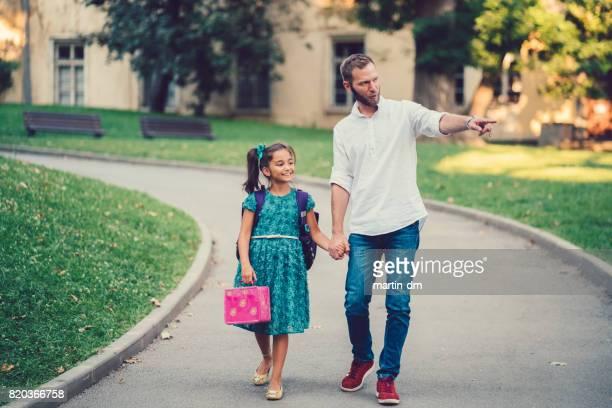 Vater führt seine Tochter zur Schule