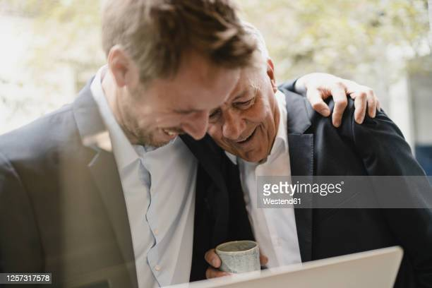 father leaning on shoulder of his son, looking at laptop, smiling - sohn stock-fotos und bilder