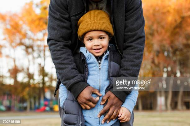 Father leaning over son in park