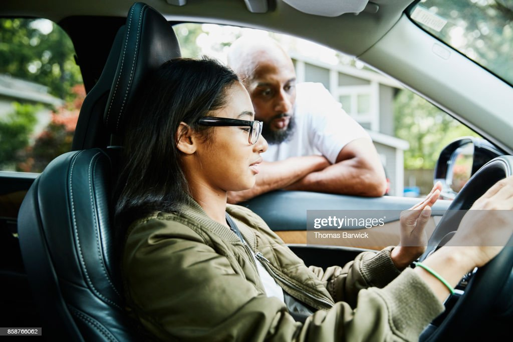 Father leaning through window of car while teaching daughter to drive : Stock Photo
