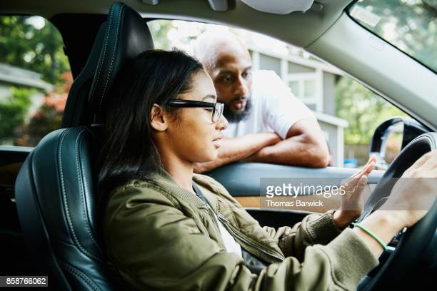 father leaning through window of car while teaching daughter to drive - family inside car stock photos and pictures