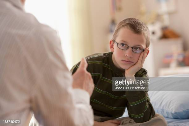 father lecturing son in bedroom - penalty stock pictures, royalty-free photos & images