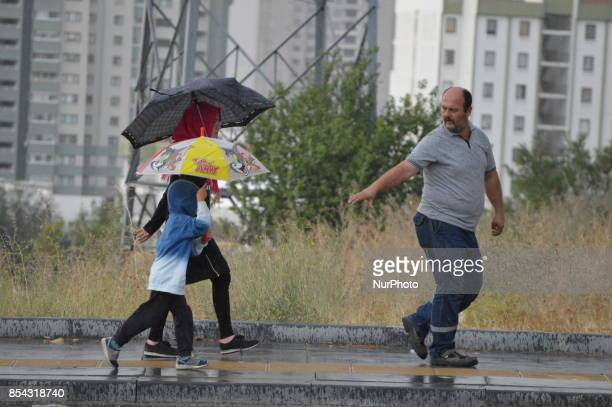 A father lends a hand to his son as they walk on a raindrenched road during a rainy autumn day in Ankara Turkey on September 26 2017 The temperature...