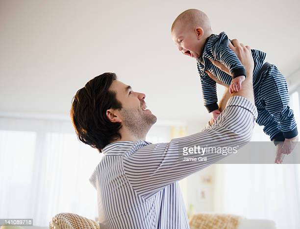 father lifting baby boy in air - sollevare foto e immagini stock