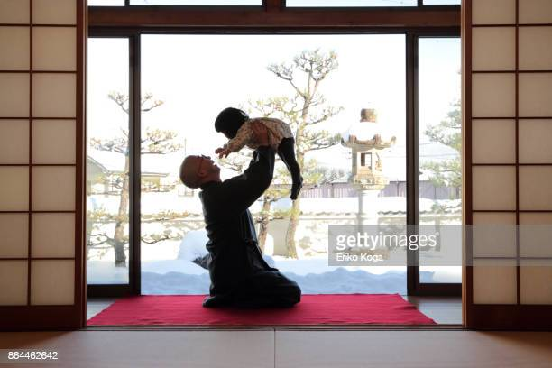 Father lifting baby up in background of snowy garden