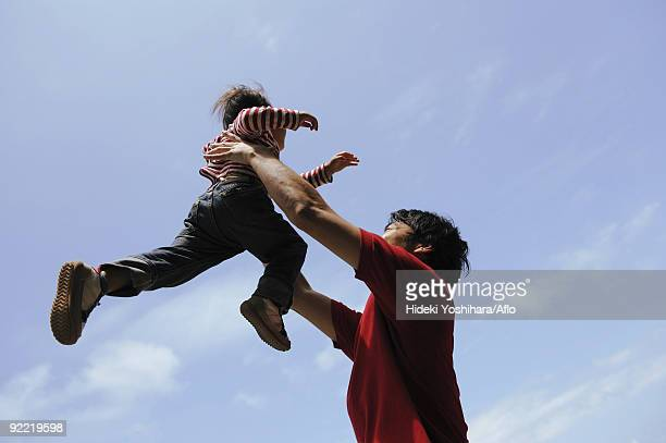 Father lifting child into air