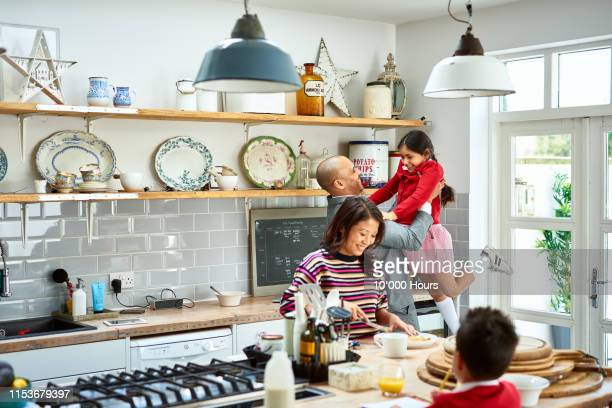father lifting daughter and smiling as mother makes breakfast - family stock pictures, royalty-free photos & images