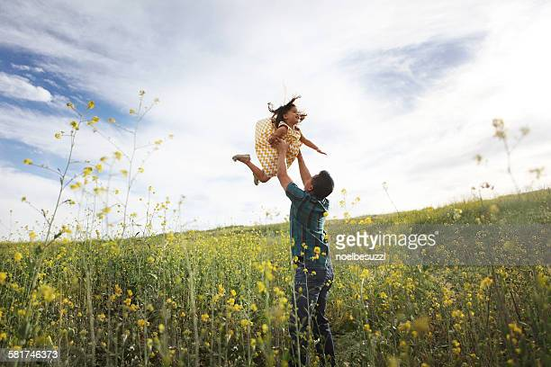 Father lifting daughter in the air