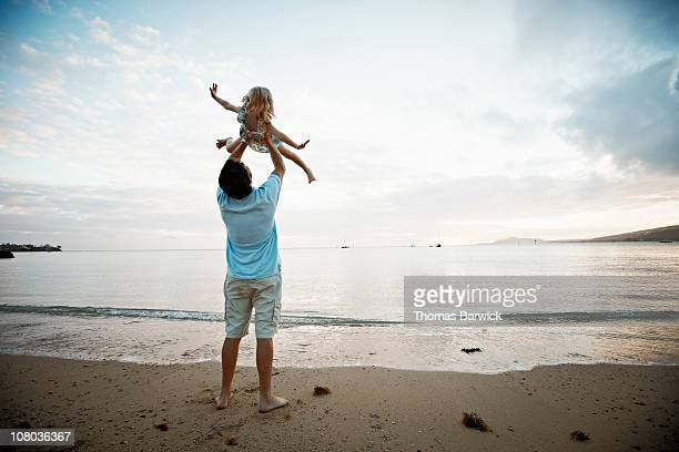 father lifting daughter overhead at sunset - sollevare foto e immagini stock