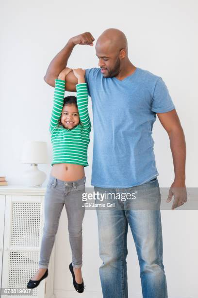 father lifting daughter using biceps - flexing muscles stock pictures, royalty-free photos & images