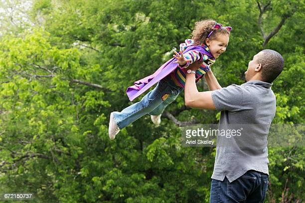 Father lifting flying superhero daughter