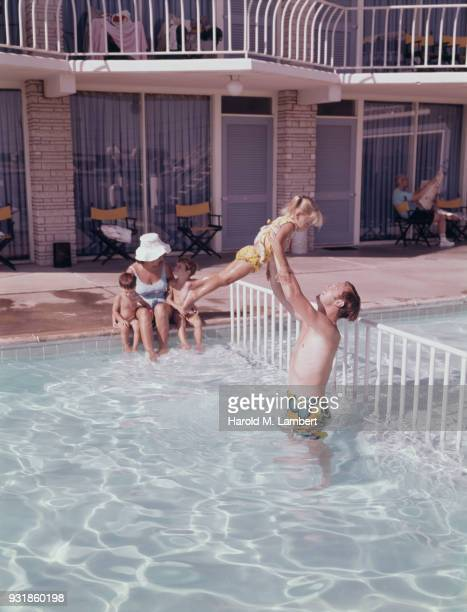 Father lifting her daughter in swimming pool while mother and their children sitting in background