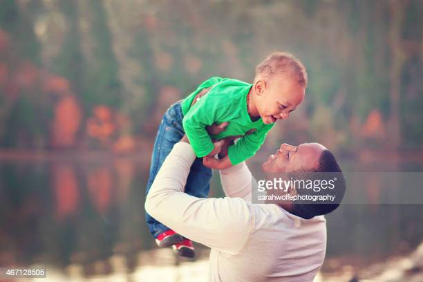 father lifting his baby in the air