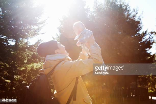 Father lifting his baby up outdoor