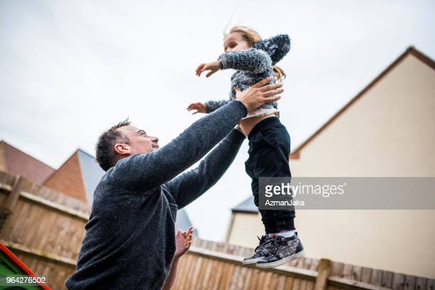 Father lifting his daughter in the air playfully