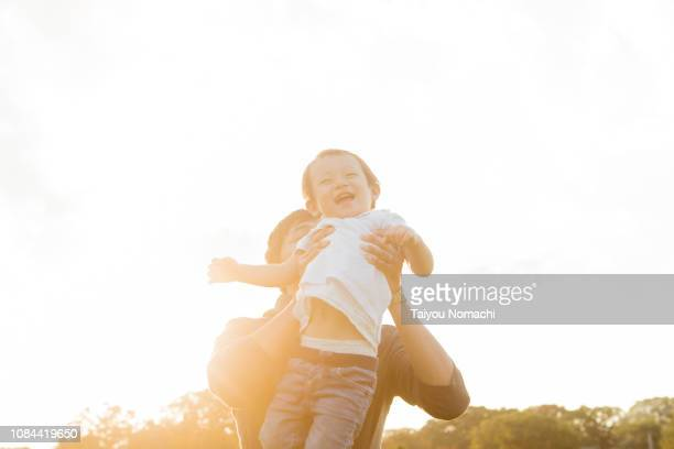 a father lifting his son - forever young stock pictures, royalty-free photos & images