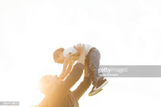 a father lifting his son - innocence stock pictures, royalty-free photos & images