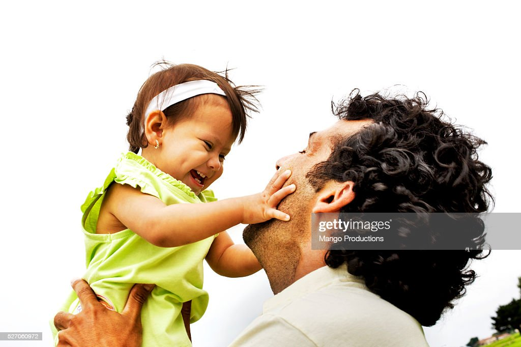 Father lifting little girl up : Stock Photo