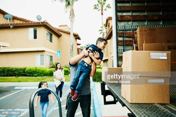 father lifting smiling son into back of moving truck - physical activity stock pictures, royalty-free photos & images