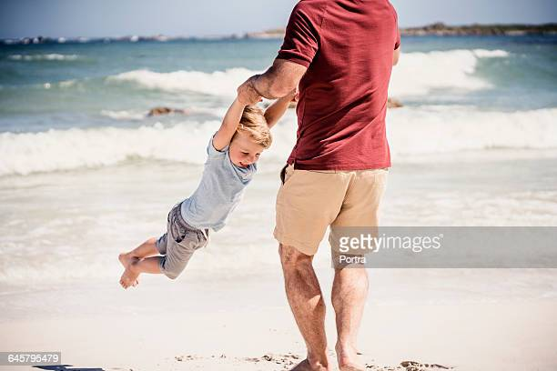 Father lifting smiling son over shore on sunny day