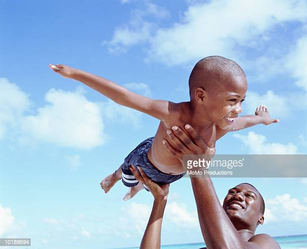 Father lifting son (6-8 years) in air at beach, son pretending to fly