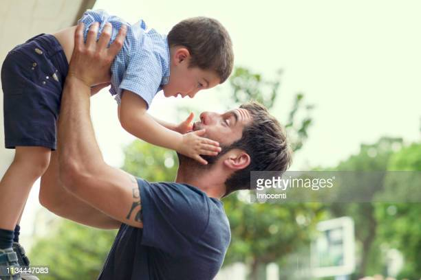 father lifting son - sollevare foto e immagini stock