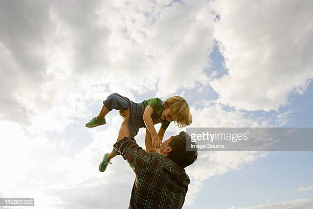 father lifting son up to the sky - picking up stock pictures, royalty-free photos & images