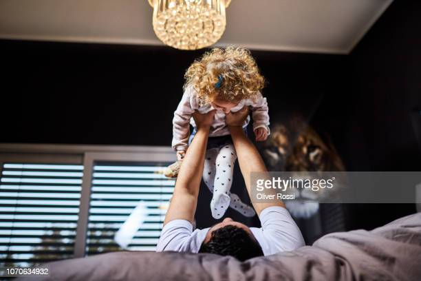 Father lifting up daughter in bed