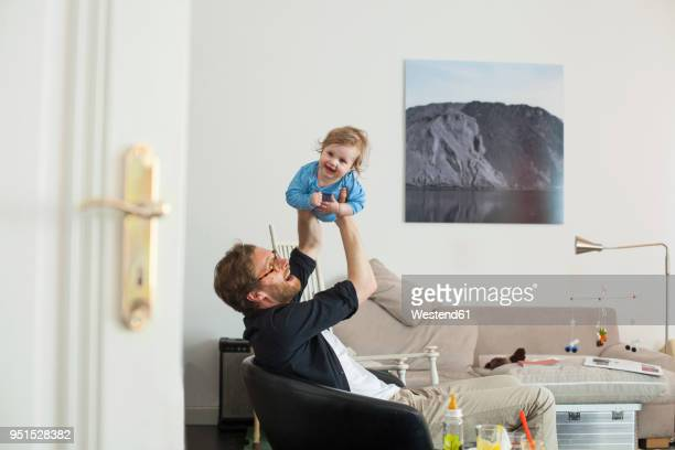 father lifting up his daugther in living room - smooth stock pictures, royalty-free photos & images