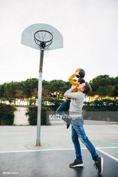 father lifting up son on basketball outdoor court - man with big balls stock photos and pictures