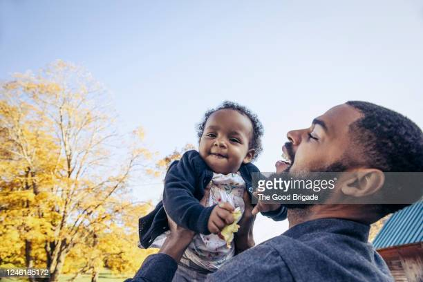 father lifting young daughter in air against blue sky - genderblend stock pictures, royalty-free photos & images