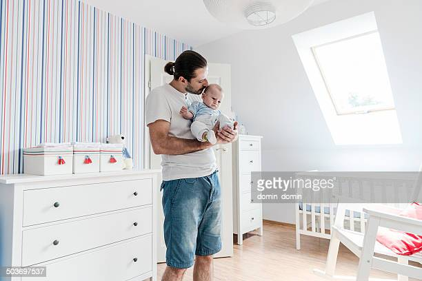 Father looking after his son, holding baby boy on hands