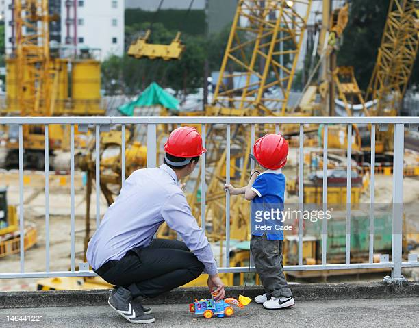 father looking at building site with young son