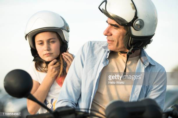 father looking at daughter fastening motorcycle helmet - スポーツヘルメット ストックフォトと画像