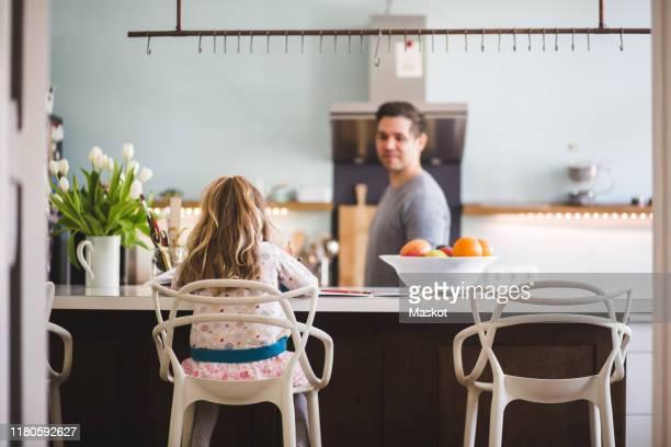 father looking at daughter studying while sitting in kitchen - alleenstaande vader stockfoto's en -beelden