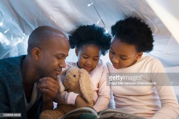 father looking at daughters reading picture book - bedtime stock pictures, royalty-free photos & images