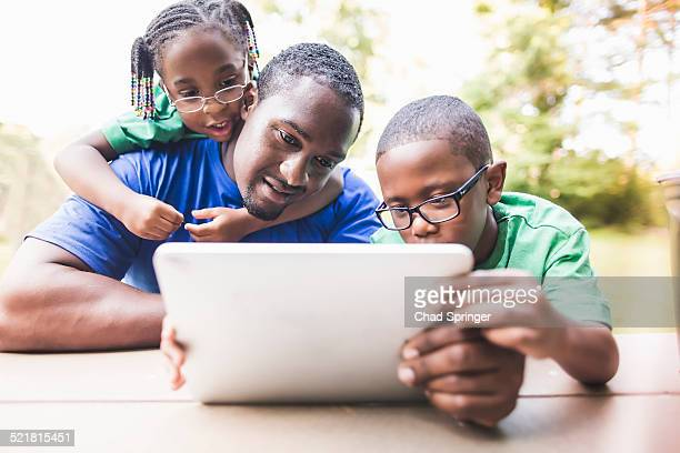 Father looking at digital tablet with daughter and son at eco camp