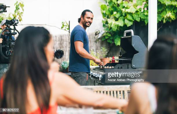 Father looking at family while preparing barbecue for them.