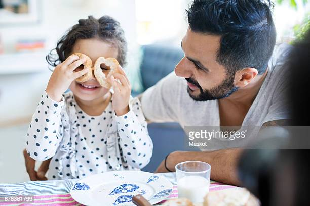 Father looking at girl playing with bread slices during breakfast