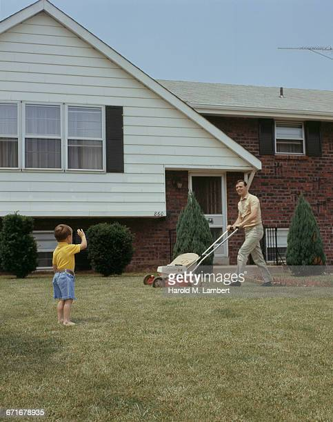 Father Looking At His Son While Mowing In Backyard