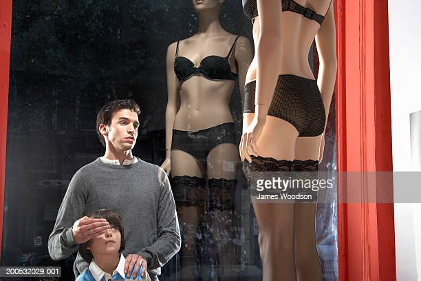 Father looking at mannequin in lingerie, covering son's eyes (7-9)