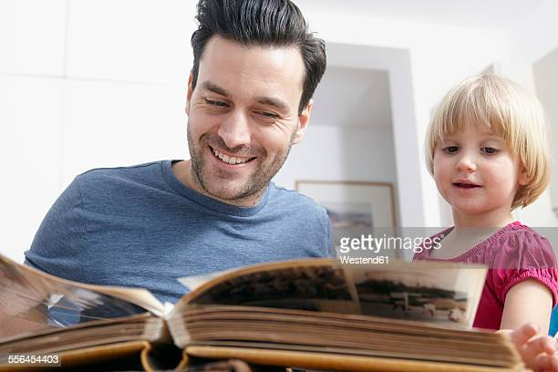 father looking at photo album with kids - childhood photo album stock photos and pictures