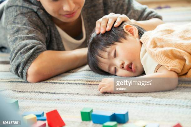 father looking at sleeping boy on carpet - 昼寝 ストックフォトと画像