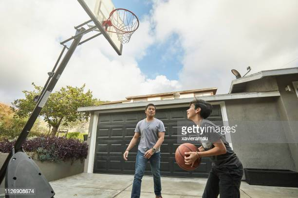father looking at son making basketball score - taking a shot sport stock pictures, royalty-free photos & images