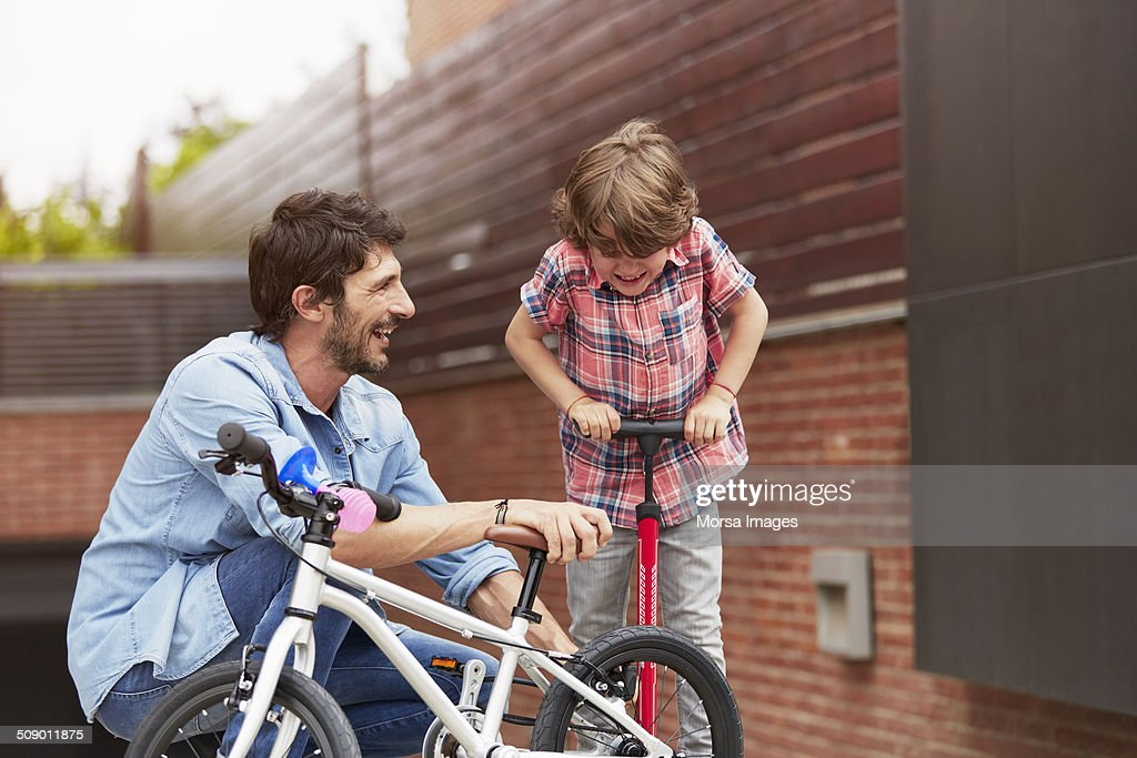 Father looking at son pumping bicycle tire : Stock Photo