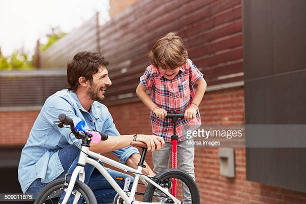 father looking at son pumping bicycle tire - air pump stock photos and pictures