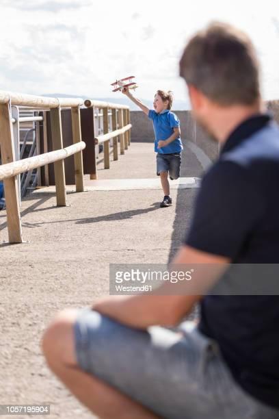 father looking at son running with toy plane - uferpromenade stock-fotos und bilder
